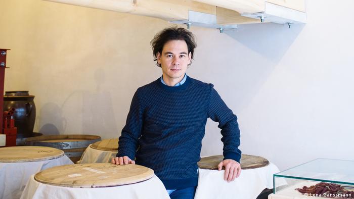 Markus Shimizu steht in seinem Geschäft Mimi Ferments neben großen Fässern. (Lena Ganssmann)