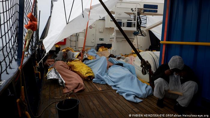 Migranten liegen auf dem von der deutschen Rettungsgesllschaft Sea-Eye betriebenen Alan Kurdi Migrantenrettungsschiff im Mittelmeer auf dem Boden.