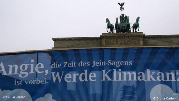 Άντζι, η εποχή του Ναι τελείωσε, γίνε Καγκελάριος του Κλίματος αναφέρει το πλακάτ στην Πύλη του Βρανδεμβούργου.