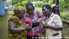 A group of women in Kenya look at a mobile phone together (Imago Images/photothek/T. Imo)