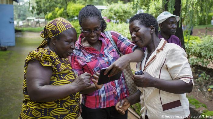 Three Kenyan women look at the screen of a mobile phone held by the woman in the middle