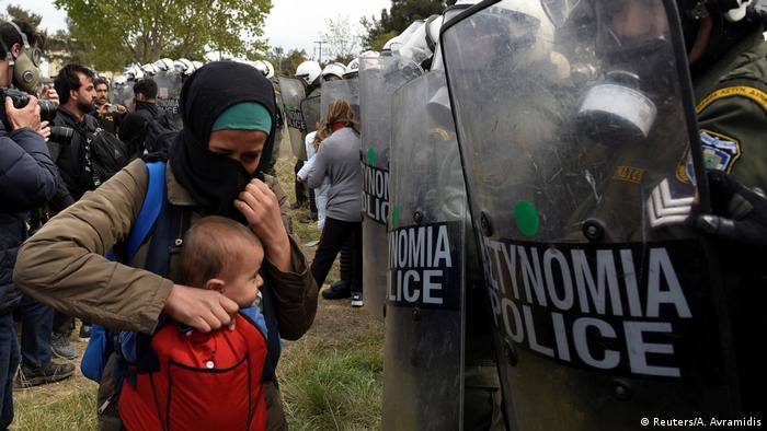 A refugee holds her child in front of Greek police in Diavata (Reuters/A. Avramidis)