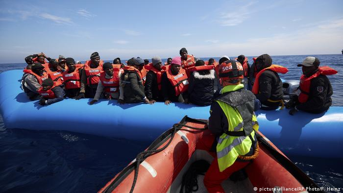 Migrants on a rubber dinghy are approached by Sea-Watch rescue ship's staffers in the waters off Libya