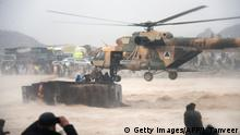 TOPSHOT - In this photo taken on March 2, 2019, an Afghan military helicopter rescues people from atop an overturned truck in flooded area of Arghandab district in Kandahar province. - At least 20 people were killed by flash floods in southern Afghanistan's Kandahar province, the UN said on March 2, 2019, as heavy rains swept away homes and vehicles and potentially damaged thousands of houses. (Photo by JAVED TANVEER / AFP) (Photo credit should read JAVED TANVEER/AFP/Getty Images)