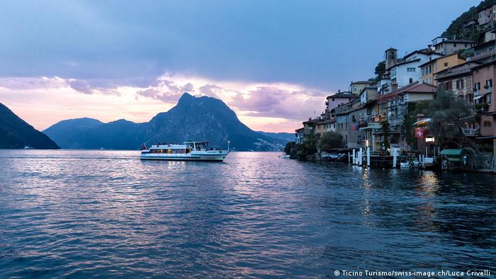 Lake Lugano at sunset - mountains in the background and a boat approaching a lake village in the foreground - Evening boat trip on Lake Lugano arriving in Gandria (Ticino Turismo/swiss-image.ch/Luca Crivelli )