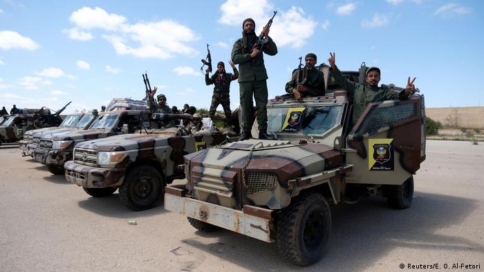 Libyan National Army (LNA) members, commanded by Khalifa Haftar, pose for a picture with their weapons as they head out of Benghazi to reinforce the troops advancing to Tripoli