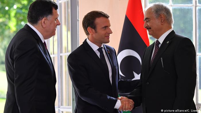 French President Emmanuel Macron (center) shakes hands with Libyan general Khalifa Haftar while standing next to UN-backed leader Fayez al-Sarraj