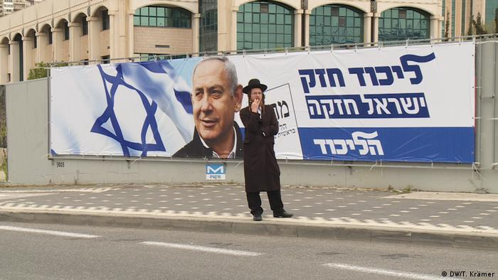 Muškarac obučen ortodoksno ispred izbornog plakata Netanjahua