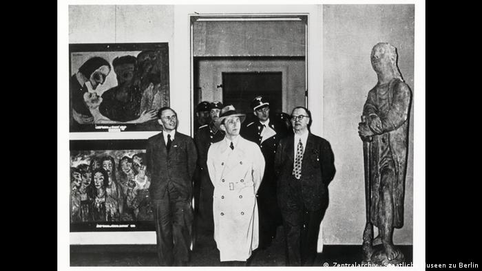 Joseph Goebbels and others at the exhibtion Degenerate Art with paintings on the left and a statue to the right.