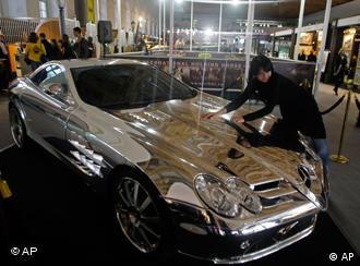 A man polishes a silver Kamrus Mercedes SLR 750