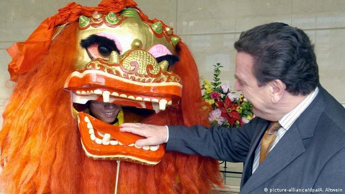 Шрёдер кладет руку в пасть китайского дракона
