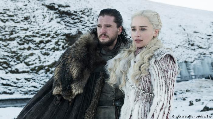 A man and women stand in the snow wearing fur