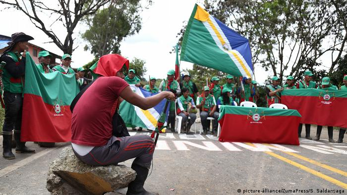 Colombian protesters hold flags as they block a highway