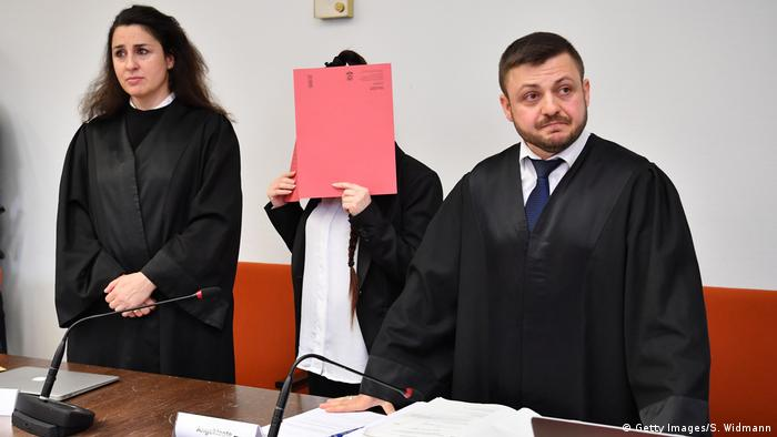 A woman, flanked by lawyers, holds a folder in front of her race to avoid being photographed (Getty Images/S. Widmann)