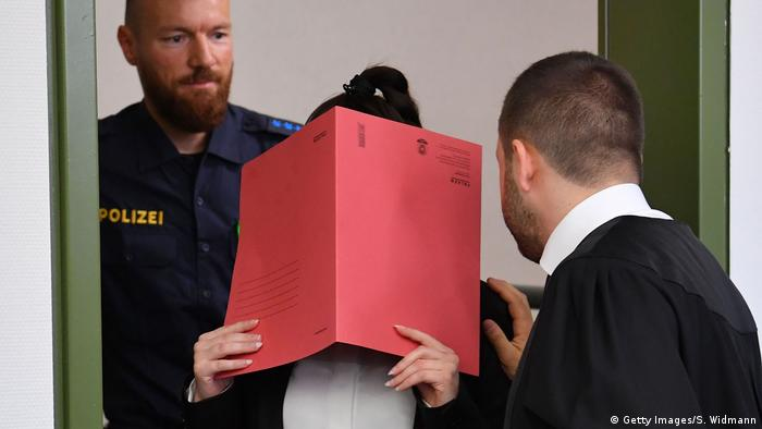 Jennifer W. in court, covering her face with a folder (Getty Images/S. Widmann)