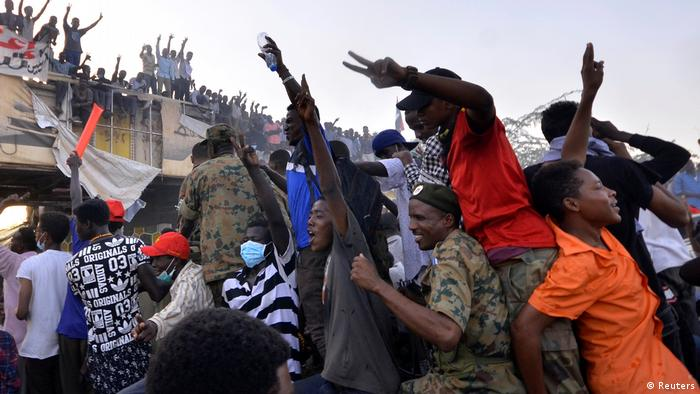 A crowd of demonstrators in Sudan cheer and wave their hands
