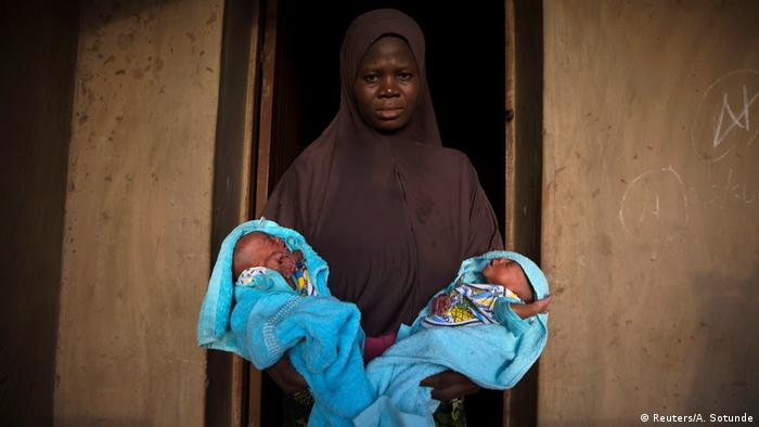 A woman with her twin babies (Reuters/A. Sotunde)