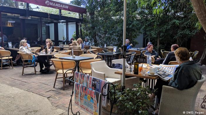 People sit at a cafe in Haifa