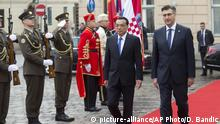 China's Premier Li Keqiang, center and Croatia's Prime Minister Andrej Plenkovic review honor guards during an arrival ceremony in Zagreb, Croatia, Wednesday, April 10, 2019. The Chinese Prime Minister is on a state visit to Croatia. (AP Photo/Darko Bandic) |