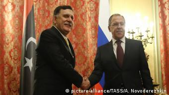 Libya's Prime Minister Fayez Sarraj (L) and Russia's Foreign Minister Sergei Lavrov shake hands at a meeting