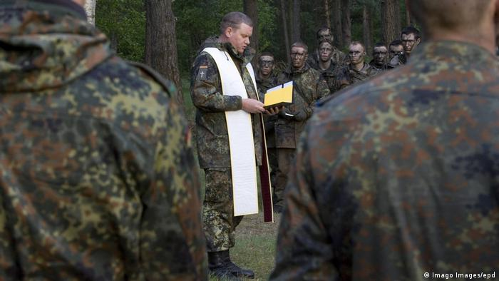 A German military chaplain holds a service in the field for Bundeswehr recruits