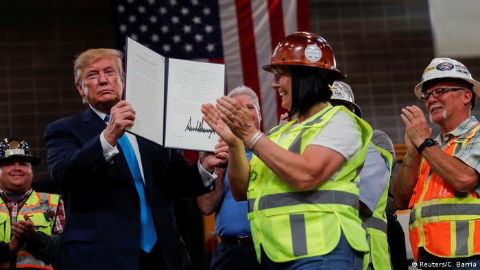 U.S. President Donald Trump displays an executive order he signed on energy and infrastructure as workers applaud at the International Union of Operating Engineers International Training and Education Center in Crosby, Texas, U.S., April 10, 2019. REUTERS/Carlos Barria