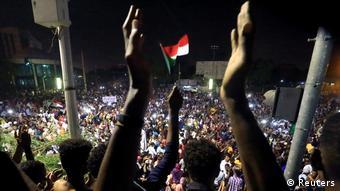 Флаг Судана и протестующие в Хартуме, 10 апреля 2019 года
