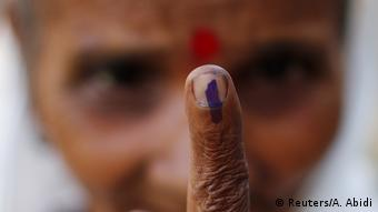 A woman show her ink-marked finger after casting her vote