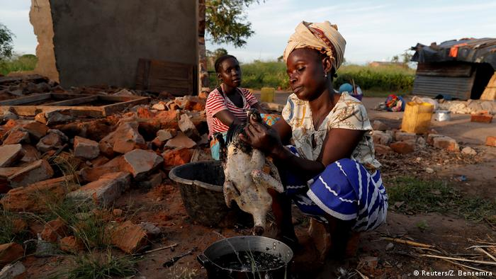 Women displaced by a cyclone in Mozambique are preparing food in the ruins of a house