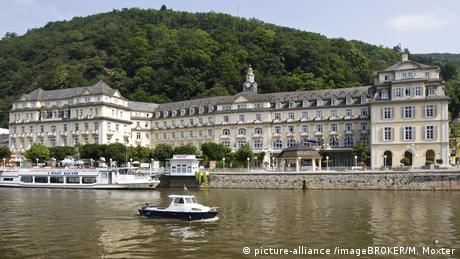 Blick auf Häcker's Kurhotel in Bad Ems. Auf der Lahn, die im Vordergrund zu sehen ist, ankern Ausflugsboote.