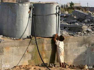 Wassertanks in der West Bank aus denen ein Kind trinkt. (AP Photo/Adel Hana, File)