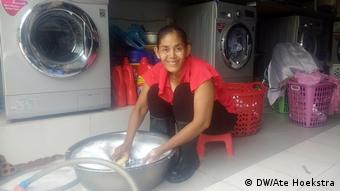 Moung San hand-washing her clothes at her laundry service
