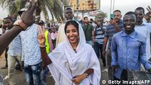Alaa Salah, a Sudanese woman propelled to internet fame earlier this week after clips went viral of her leading powerful protest chants against President Omar al-Bashir, flashes the victory gesture and shouts slogans while marching during a demonstration in front of the military headquarters in the capital Khartoum on April 10, 2019. - In the clips and photos, the elegant Salah stands atop a car wearing a long white headscarf and skirt as she sings and works the crowd, her golden full-moon earings reflecting light from the fading sunset and a sea of camera phones surrounding her. Dubbed online as Kandaka, or Nubian queen, she has become a symbol of the protests which she says have traditionally had a female backbone in Sudan. (Photo by - / AFP) (Photo credit should read -/AFP/Getty Images)