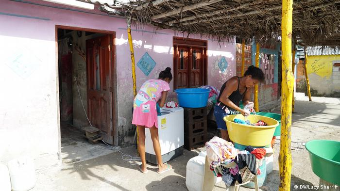 Two women wash clothes in Boca Chica, Tierra Bomba, Colombia