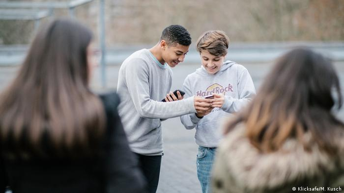 Two boys looking at a smartphone screen and laughing