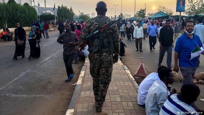 A soldier walks amid protesters in Khartoum, Sudan