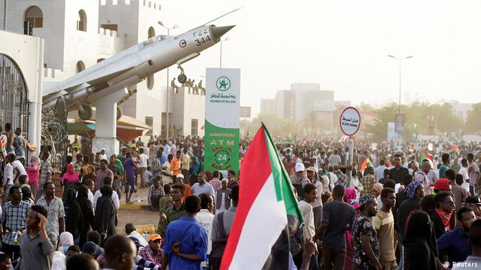 Sudanese demonstrators hold national flags as they sit outside the Defense Ministry in Khartoum
