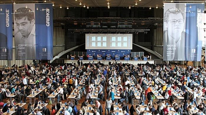 Huge auditorium with row upon row of people seated at tables, playing chess