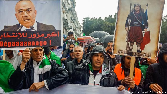 Algerians hold up signs depicting former prime minister Ahmed Ouyahia (R) dressed as a Zouave
