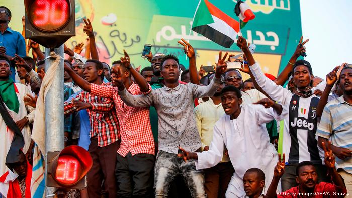 Sudanese demonstrate for democracy by waving flags and cheering (Getty Images/AFP/A. Shazly)