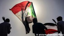 13.04.2019, Sudan, Khartum: Sudanesische Demonstranten schwenken Nationalflaggen bei einer Kundgebung, um die Bildung einer Zivilregierung zu fordern. Erst wurde Sudans Langzeitherrscher Al-Baschir abgesetzt, und nur einen Tag später musste der Chef des militärischen Übergangsrates seinen Hut nehmen. Die Demonstranten geben nicht auf. Foto: Uncredited/AP/dpa +++ dpa-Bildfunk +++