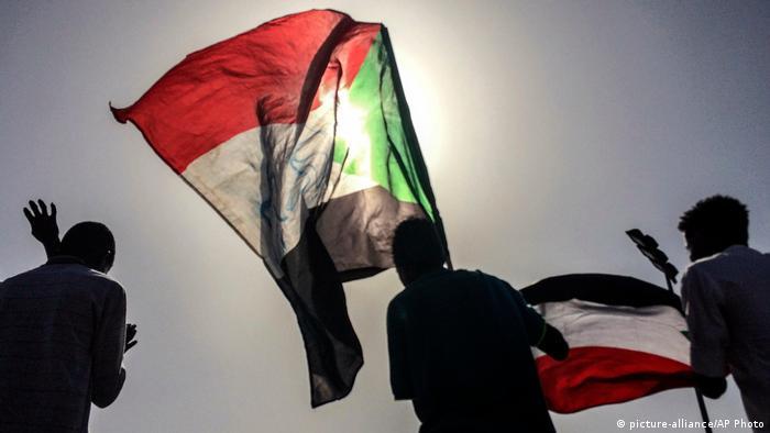 Силуэты людей с флагами Судана в руках