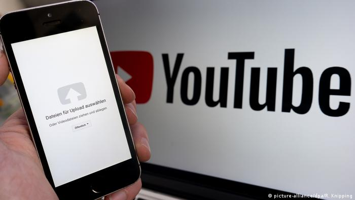 Mobile phone showing upload symbol with YouTube logo on computer screen behind