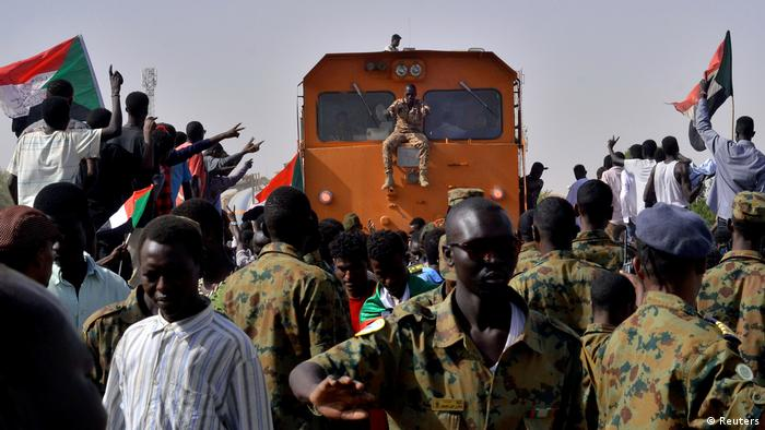 Sudanese protesters attending a sit-in block a train passing through in Khartum