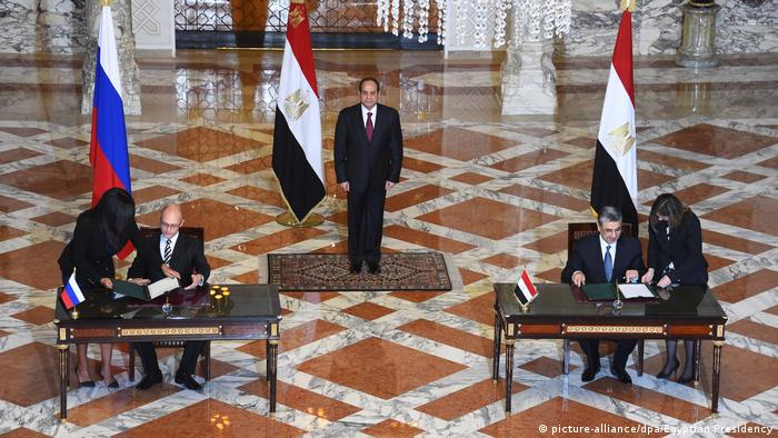Ministers sign an agreement at tables with the Russian and Egyptian flags behind them