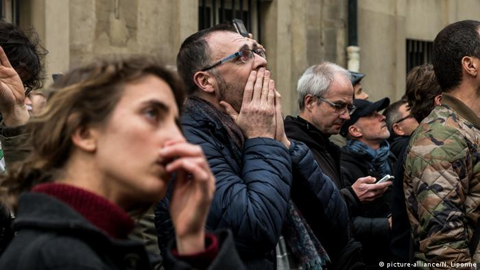 People watch as Notre Dame Cathedral in Paris burns (picture-alliance/N. Liponne)