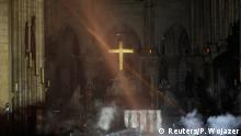 Smoke rises around the altar in front of the cross inside the Notre Dame Cathedral (Reuters/P. Wojazer)
