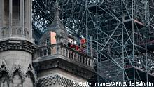 Firefighters work to extinguish a fire at Notre-Dame Cathedral in Paris early on April 16, 2019. - A huge fire that devastated Notre-Dame Cathedral is under control, the Paris fire brigade said early on April 16 after firefighters spent hours battling the flames. (Photo by STEPHANE DE SAKUTIN / AFP) (Photo credit should read STEPHANE DE SAKUTIN/AFP/Getty Images)