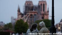 A couple looks on as firefighters work to extinguish a fire at Notre-Dame Cathedral in Paris early on April 16, 2019. - A huge fire that devastated Notre-Dame Cathedral is under control, the Paris fire brigade said early on April 16 after firefighters spent hours battling the flames. (Photo by Zakaria ABDELKAFI / AFP) (Photo credit should read ZAKARIA ABDELKAFI/AFP/Getty Images)