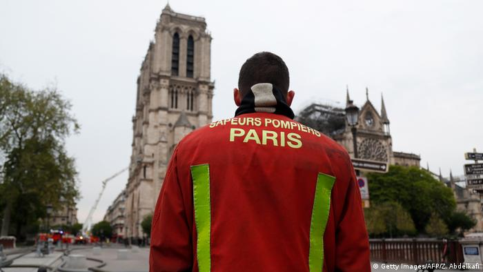 A firefighter observes the damage to Notre Dame the morning after the blaze